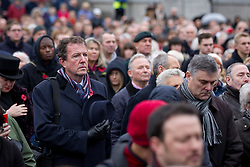 © Licensed to London News Pictures. 11/11/2013. London, UK. Members of the public pause for thought during the two minutes silence honouring war dead at the 'Silence in the Square' ceremony, held by the Royal British Legion, in Trafalgar Square, London, today (11/11/2013). The ceremony, culminating in a countrywide two minutes silence and the placing of poppies into the square's fountains, is held on the 11th hour of the 11th day to commemorate the signing of the armistice that ended the First World War.  Photo credit: Matt Cetti-Roberts/LNP