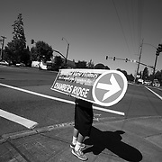 Businesses from restaurants to massage parlors and home builders took advantage of the influx of tourists to advertise their wares. A young man on the main road to the golf course twirls a sign advertising new homes near Chambers Bay, the site of the 2015 US Open.