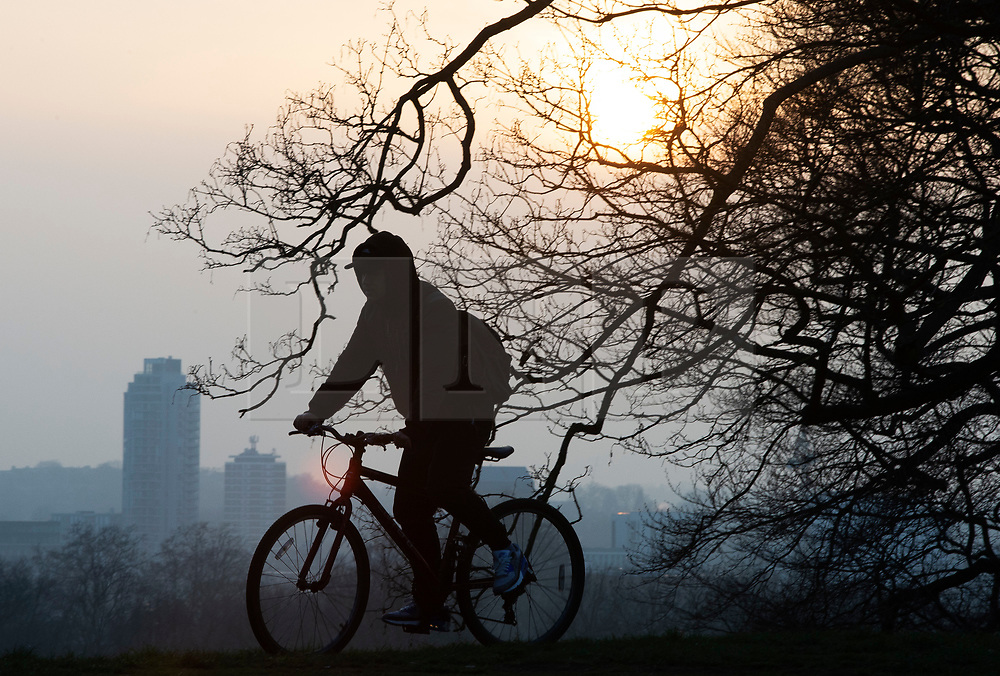 © Licensed to London News Pictures 02/03/2021. Greenwich, UK. A cyclist getting ready to watch the sunset. People get out of their homes from a third national Coronavirus lockdown to enjoy the sunset in Greenwich Park, London. Photo credit:Grant Falvey/LNP