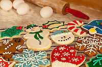 Variety of decorated Christmas sugar cookies with red-handled rolling pin and fresh eggs in the background.
