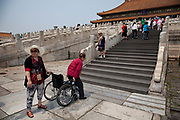 Elderly woman gets up from her wheelchair to climb the steps to the Hall of Supreme Harmony inside The Forbidden City, a Chinese imperial palace from the Ming Dynasty to the end of the Qing Dynasty. It is located in the middle of Beijing, China, and now houses the Palace Museum. For almost 500 years, it served as the home of emperors and their households, as well as the ceremonial and political center of Chinese government. Built in 1406 to 1420, the complex consists of 980 buildings. The palace complex exemplifies traditional Chinese palatial architecture, and has influenced cultural and architectural developments in East Asia and elsewhere. The Forbidden City was declared a World Heritage Site in 1987, and is listed by UNESCO as the largest collection of preserved ancient wooden structures in the world.
