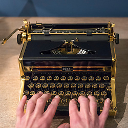 "© Licensed to London News Pictures. 26/10/2018. LONDON, UK. A staff member presents ""The Golden Royal Portable"", an 18 carat gold plated typewriter (Est GBP800-1,200).   Preview of ""A Private View, property from the country home of Christopher Cone and Stanley J. Seeger"" at Sotheby's, New Bond Street.  Over 200 extraordinary works will be auctioned in London on 30 October 2018.  Photo credit: Stephen Chung/LNP"