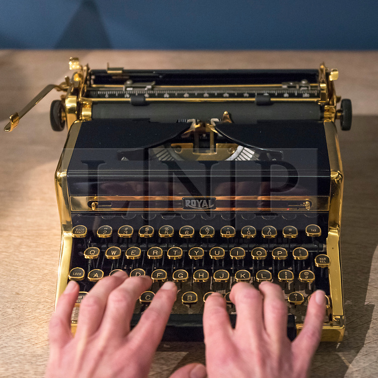 """© Licensed to London News Pictures. 26/10/2018. LONDON, UK. A staff member presents """"The Golden Royal Portable"""", an 18 carat gold plated typewriter (Est GBP800-1,200).   Preview of """"A Private View, property from the country home of Christopher Cone and Stanley J. Seeger"""" at Sotheby's, New Bond Street.  Over 200 extraordinary works will be auctioned in London on 30 October 2018.  Photo credit: Stephen Chung/LNP"""