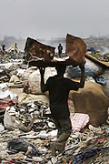 Olusosum dump site, Lagos.  Goverment run by the agency Lagos Waste Management Authority ( LAWMA ). One of 6 sites taking in general waste from all over Lagos.  E-waste is not allowed on site, but some does appear from the gerneral waste  collected all over Lagos.  People, are making a living out of shifting through the rubbish and selling their collections for recycling.Some of the scavengers live on site, too poor to pay for accommodation any where else. This picture is part of an undercover investigation by Greenpeace and Sky News.  A TV-set originally delivered to a municipality-run collecting point in UK for discarded electronic products was tracked and monitored by Greenpeace using a combination of GPS, GSM, and an onboard radiofrequency transmitter placed inside the TV-set.  The TV arrived in Lagos in container no 4629416 and was found in Alaba International Market and bought back by Greenpeace activist. The TV was subsequently brought back to England and used as proof of illegal export of electronic waste. A number of individual are currently on trial in London in connection with illegal exports(Nov 2011)