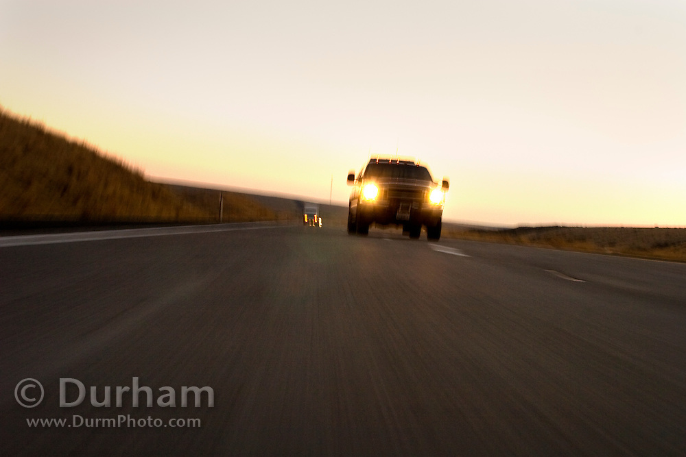 A gasoline powered truck races down interstate 84 at dusk. Oregon.