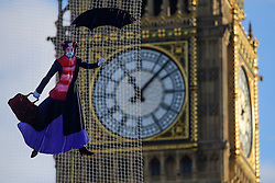 © Licensed to London News Pictures. 06/01/2017. London, UK. An image of Mary Poppins wearing a face mask is suspended from a balloon in front of Big Ben during a  Greenpeace protest about air pollution in Parliament Square. Photo credit: Ben Cawthra/LNP