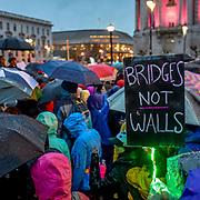 "Marchers in umbrellas and rain coats make slow progress from City Hall toward Market Street.  A sign reads, ""Bridges not walls."""