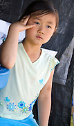 Cute 5 year old Hmong child deep in thought. Hmong Sports Festival McMurray Field St Paul Minnesota USA