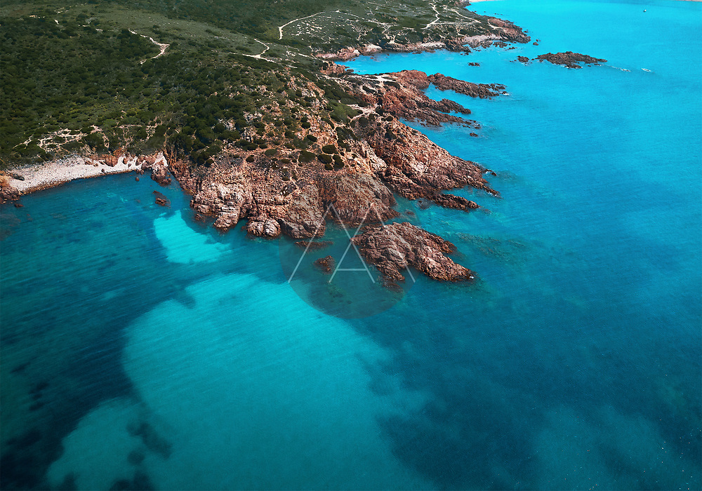Aerial view of a reddish cliff surrounded by spectacular turquoise waters near Isola Rossa, Sardinia, Italy.