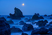 A full moon sets while coming out of an eclipse at Furlong Gulch, Sonoma Coast State Park, California