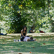 London,England,UK, 26th Aug 2016 : A ladies giving a massage to her boyfriend and enjoy the August Summer weather in Green park, London. See Li/Picture Capital