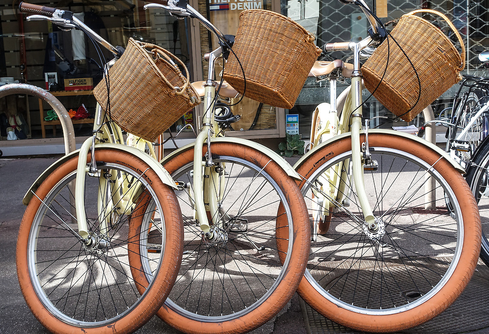 Three standing bicycles, front wheels interlocking, with cream bodywork, reddish brown tires and straw baskets, are parked on a street in Antibes, France.