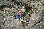 LIANGSHAN, CHINA - MAY 14: (CHINA OUT) <br /> <br /> A pupil from Atuler village climbs vines hung on the cliff to go home after school on May 14, 2016 in Liangshan Yi Autonomous Prefecture, Sichuan Province of China. 72 families lived in Atuler village on the 800-meter cliff at Meigu River Canyon in Liangshan Yi Autonomous Prefecture. 15 pupils, aged 6 to 15, accompanied by 3 adults regularly spent 2 hours climbing 17 vines ladders hung on the 800-meter-high cliff to go between school and home twice a month. Villagers used the same ladders to go to the nearest market once a week to sell peppers and walnuts and buy necessities. <br /> ©Exclusivepix Media