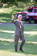 US President Bill Clinton waves as he walks across the South Lawn of the White House to board Marine One helicopter as he departs for the Governors Conference in Vermont on the South Lawn of the White House July 31, 1995 in Washington, DC.
