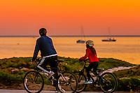 Riding bicycles at sunset (East Beach behind), Santa Barbara, California USA.