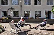 Nederland, Nijmegen, 10-4-2020 De binnenstad van Nijmegen is zo goed als leeg . Het is duidelijk rustiger en stiller in de straten, winkelstraten van het centrum in de stad . Mensen blijven thuis om zo min mogelijk risico te nemen ivm het corona virus . In een hofje zitten drie buurtbewoners buiten met elkaar te praten. Ze houden 1,5 meter afstand .Foto: Flip Franssen