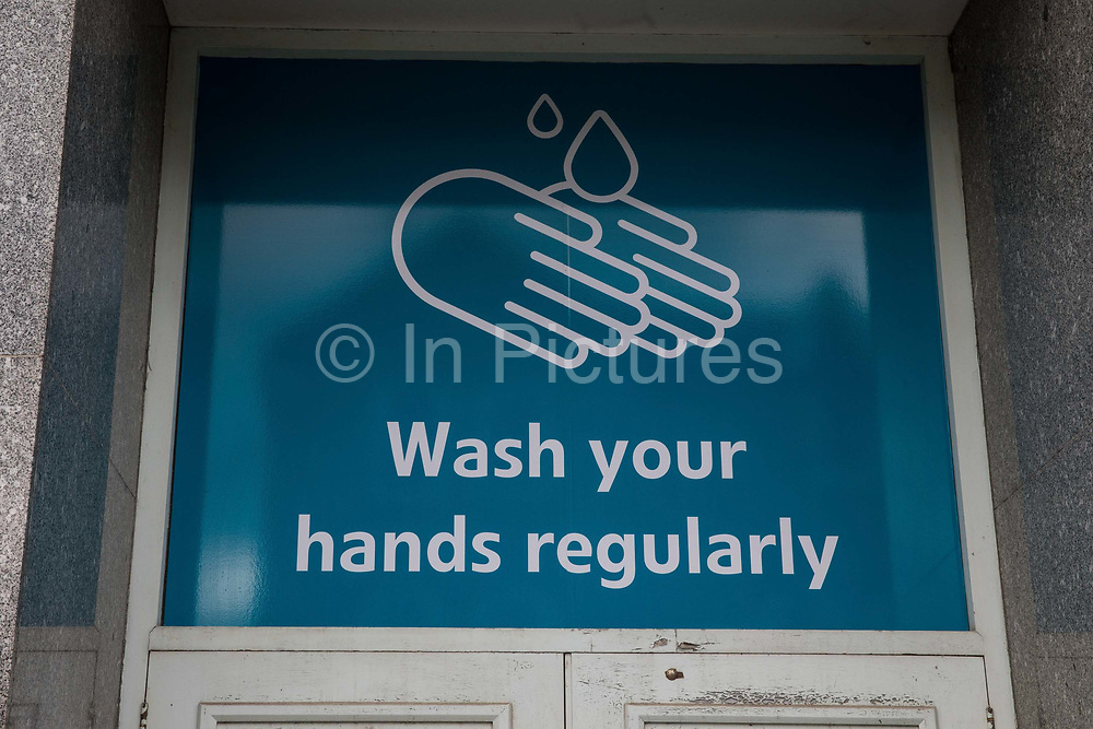 A poster advising members of the public to wash their hands regularly is displayed above a shop doorway on 21st August 2020 in Slough, United Kingdom. Slough has been listed by Public Health England PHE and the Department for Health and Social Care DHSC as an 'area of concern' for COVID-19 following a rise in positive coronavirus cases over the last two weeks.