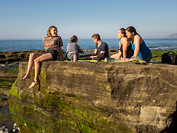 Group of young friends sitting on rocky beach at Playa de Azkorri, Getxo, Basque Country, Spain