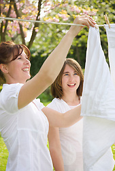 Smiling woman and teenaged girl hanging linens on a clothesline