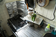 corner of kitchen sink with cooking stove and stacked food Japan