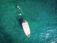 Aerial view of people swimming from a boat in the Tyrrhenian Sea, near Procida, off the coast of Naples in Southern Italy.