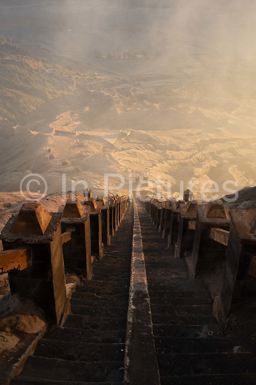 Mount Bromo Gunung Bromo seen at dawn on 11th June 2018, East Java, Indonesia. The active volcano is park of the Bromo Tengger National Park, sitting on a plain called the sea of sand, it is possible to look into the crater of the volcano to see the smoke and steam emerging from it, lava is not visible.