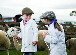 © Licensed to London News Pictures.29/07/15<br /> Borrowby, UK. <br /> <br /> Two youngsters chat as they hold onto their sheep during judging at the Borrowby Country Show and Gymkhana in North Yorkshire.<br /> <br /> Photo credit : Ian Forsyth/LNP