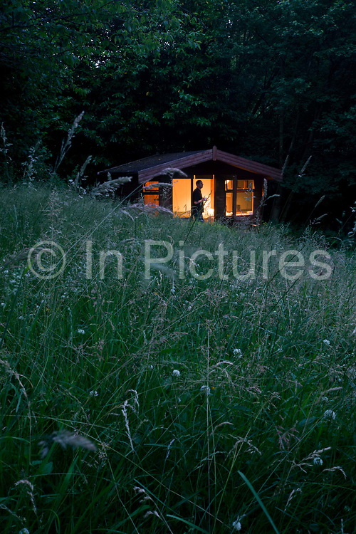 A Buddhist man on silent retreat in a private cabin at the Rivendell Buddhist Retreat Centre, East Sussex, England. As the last light from a summer's day fades into night, the cabin (a converted garden shed), the practicing Buddhist stands against the internal lamp light, pausing to think and contemplate about his life and its meaning. Long grass from a private meadow is for the sole use of someone in retreat, a period of a few days or perhaps a week, separated from the pressures of modern life. Rivendell was once a Victorian country rectory for the local vicar in this East Sussex village, it now houses facilities for the spiritual and the peaceful, having escaped for a brief time, the pressures of modern life. Beyond are two Buddhas on a tapestry and as a statue. The community web address is www.rivendellretreatcentre.com.