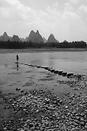 Black and white picture of a woman standing on a rocks line crossing the river Li.
