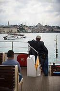 Passengers aboard a ferry crossing the Bosphorus Strait in Istanbul, Turkey.