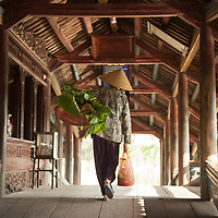 A local walks across the Thanh Toan bridge in Thanh Toan village outside of Hue, Vietnam.