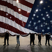 From right, David Thompson, Scott Ratliff, Angel Staten, Greg Miranda, Mike Otter, Paul Nemeth and Tim Bolen of the IATSE Local 369 bring down a large American flag after President Trump's political rally at the Big Sandy Superstore arena in Huntington, W.V., on Thursday, August 03, 2017.