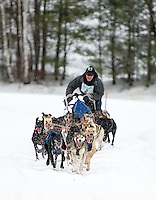 Justin Fortier and his team focus on the final hill of Friday's open class series during the 84th annual Laconia World Championship Sled Dog Races.  (Karen Bobotas/for the Laconia Daily Sun)