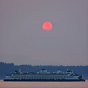 A Washington state ferry crosses Puget Sound on its way to Edmonds as the setting sun is partially obscured by wildfire smoke.