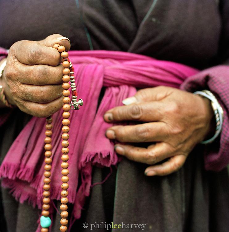 Close up of a Buddhist devotee with prayer beads, Ladakh, India