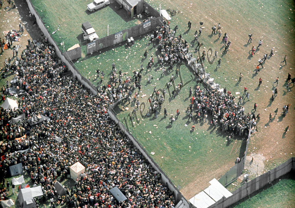 Crowds at the turnstiles - East Afton Festival Site.- .It can be seen from this aerial image, that the transport services were successful in getting all concerned to their destination. The revellers then streamed through the turnstiles and onward into the festival.