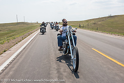 Riding north on highway 79 on the Run to the Line for lunch and biker vs Cowboy rodeo games at the Spur Creek Ranch in Newell during the annual Sturgis Black Hills Motorcycle Rally. SD, USA. Wednesday August 9, 2017. Photography ©2017 Michael Lichter.
