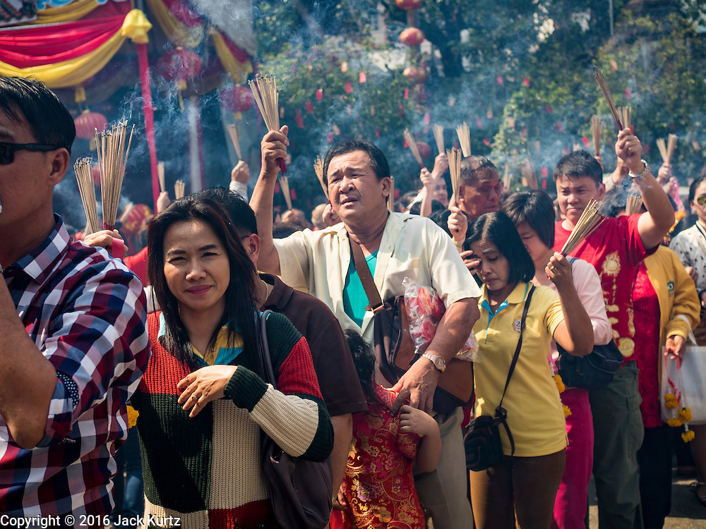 """08 FEBRUARY 2016 - BANGKOK, THAILAND: People hold incense over their heads while they wait in line to get into Wat Mangon Kamlawat, the largest Mahayana (Chinese) Buddhist temple in Bangkok during the celebration of the Lunar New Year. Chinese New Year is also called Lunar New Year or Tet (in Vietnamese communities). This year is the """"Year of the Monkey."""" Thailand has the largest overseas Chinese population in the world; about 14 percent of Thais are of Chinese ancestry and some Chinese holidays, especially Chinese New Year, are widely celebrated in Thailand.       PHOTO BY JACK KURTZ"""