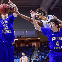 Northern Arizona University Lumberjack Felix Rivera-Vega (13) reaches over Embry-Riddle University Eagle Logan Skurdal (4) in an attempt to steal a rebound from Calvin Carmichael (35) Friday at Window Rock High School.