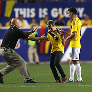 A fan runs onto the pitch to ask James Rodriguez, Colombia, for his autograph while being substituted during the Columbia Vs Canada friendly international football match at Red Bull Arena, Harrison, New Jersey. USA. 14th October 2014. Photo Tim Clayton