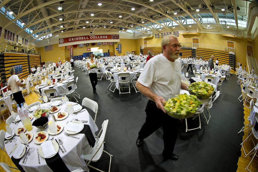 A volunteer hurriedly rushes to plate salads before the opening banquet of the NCAA Division III Indoor Track and Field Championships at Grinnell College on Thursday evening.