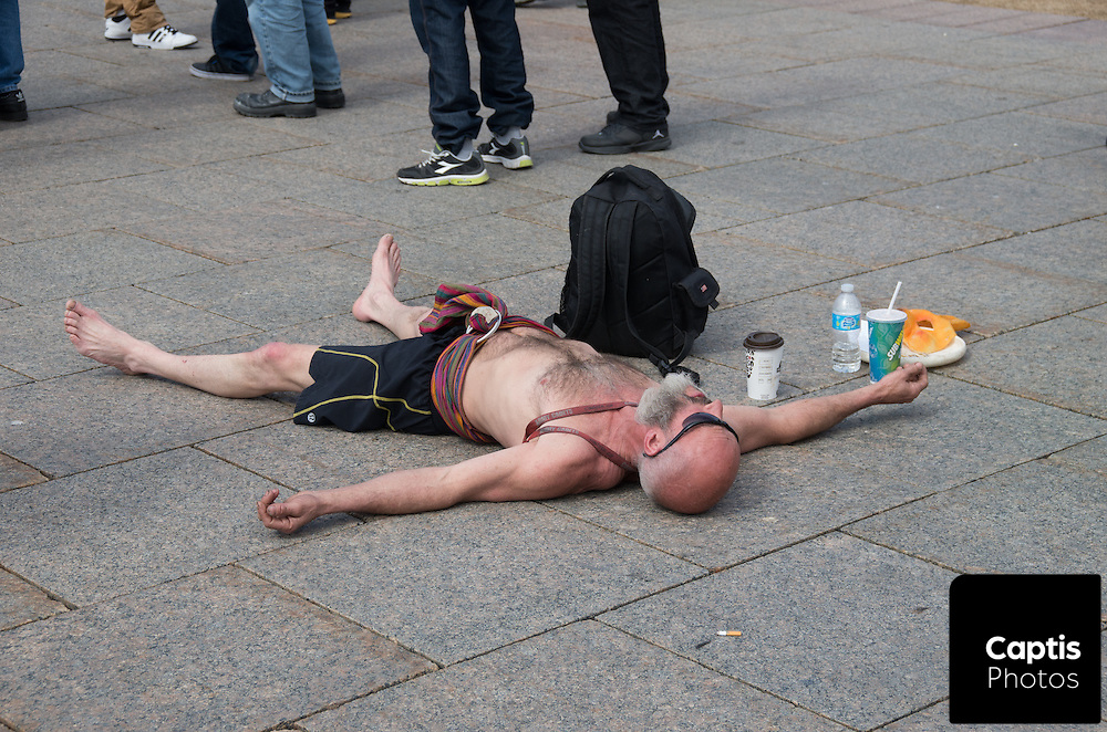 A man lies on the ground in front of Parliament Hill. April 20, 2014.