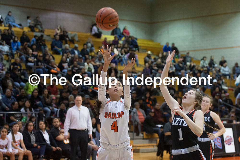 Gallup Bengal Jordan Hanley (4) takes a shot as Aztec Tiger Celiese McNeal (1) defends Tuesday night at Gallup High School in Gallup. Gallup beat the Tigers 51-11.