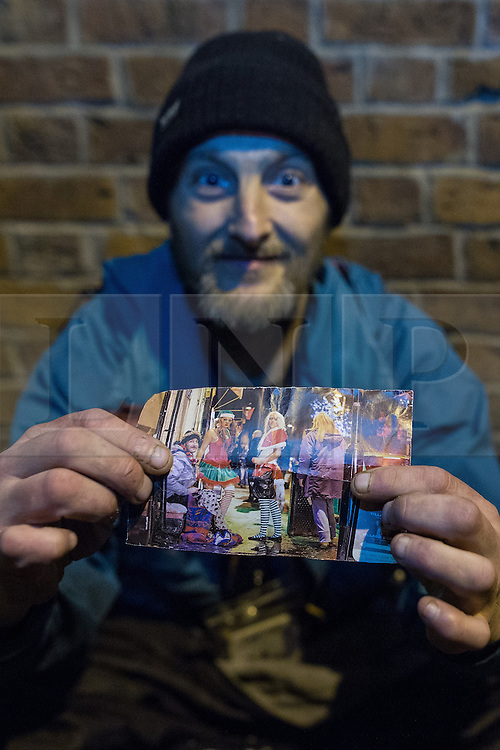 © Licensed to London News Pictures . Manchester , UK . 05/04/2015 . Homeless Darren Jones shows a folded up photograph of himself with revellers , taken by photographer Joel Goodman , which featured in the news in Christmas 2014 , which he keeps folded up in his pocket . Revellers on a Saturday night out during the Easter Bank Holiday weekend . Photo credit : Joel Goodman/LNP