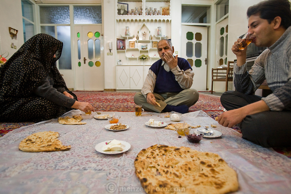 Mohammad Riahi, a part time restaurant manager and taxi driver eats breakfast with his family at their home in the city of Yazd, Iran.  (Mohammad Riahi is one of the people interviewed for the book What I Eat: Around the World in 80 Diets.)  He lives with his father and mother, and will until he marries. Even then, he and his bride will be offered the second floor of his parent's home. At the restaurant he eats whatever he feels like eating. At home though, he eats what his mother puts on the tablecloth on the floor in the middle of their living room. Many of their meals are vegetable and starch-based although they have lamb or chicken occasionally, and sheep's head soup on the weekend. As Muslims, they never eat pork.