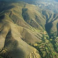 Farms outside of Cuzco huddle below foothills of the Andes. Cordillera Vilcabamba.