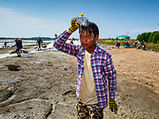 20 FEBRUARY 2019 - BAN LAEM, PHETCHABURI, THAILAND: A worker pours cold water on his head during a break from harvesting salt on one of the first days of the 2019 salt harvest in Ban Laem, Thailand. It was almost 100F during the day Wednesday. Ban Laem's salt fields are expanding because salt harvesters in Samut Sakhon and Samut Songkhram,  which are closer to Bangkok, are moving to Ban Laem as their land is turned into industrial parks.       PHOTO BY JACK KURTZ