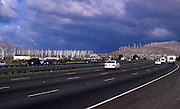Turbines of wind farm and traffic on a freeway, Palm Springs California, USA
