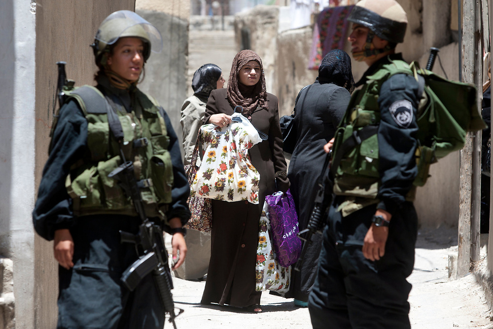Palestinian women are seen behind Israeli border policemen on patrol in the east Jerusalem neighborhood of Silwan, during a visit by the Israeli parliament committee for the children's rights to houses of Jewish families residing in a mostly Palestinian area, July 6, 2010.
