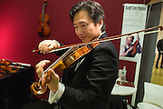 A visitor plays a violin from Scott Cao Violins, from Campbell California.
